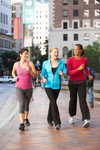 Three women power walking through a city center