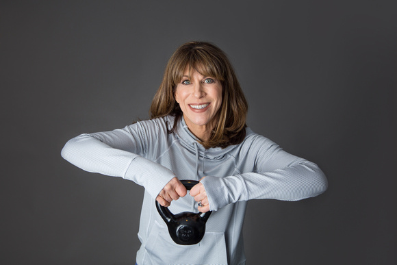 FitFortyForever creator, Judy R., in a grey hoodie lifting a 10 lb. black kettle ball.