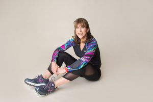 FitFitFortyForever creator, Judy R., posed in a long-sleeve, multi-colored shirt with black capri pants and blue Brooks running shoes.