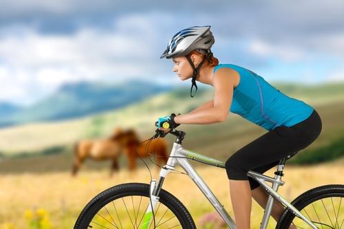 woman biking outside near horses