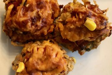 Three Mexican Turkey Meatloaf Cupcakes with cheddar cheese topping and a small amount of cilantro to the side.