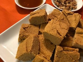Blondies made with garbanzo beans on a white plate with maple syrup and walnuts in their own individual plates on an orange setting.