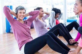 Portrait of woman doing sit ups with friends at fitness studio