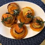 Five delicious spicy potato towers with sprigs of rosemary on a white plate ready to serve