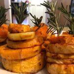Five layers of potatoes held up with sprigs of rosemary