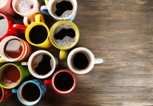 Many colorful cups of coffee on wooden background