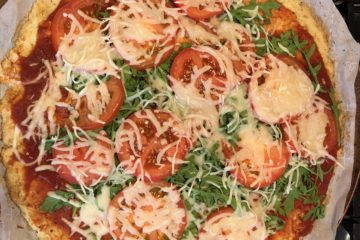 Baked cauliflower pizza toped with arugula, tomatoes and cheese, ready to slice in its pan.