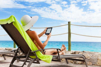 Attractive woman on the sun chair reading from electronic book