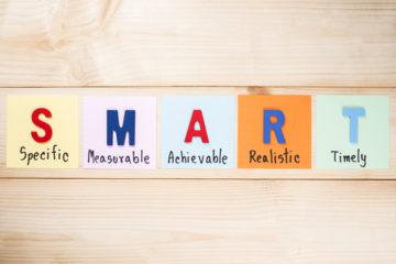 SMART Goals on wood background (Business Concept)
