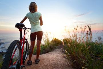 woman biking near shoreline