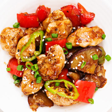 Plate of homemade low-points kung pao chicken with chopsticks against a white background